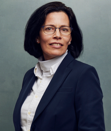Meet the Team of experts - Photo of Caroline Verheyden, person in business suit, glasses with dark frames, smiling, female, friendly, standing upright