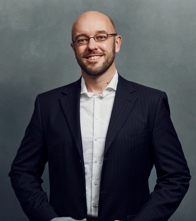 Meet the Team of experts - Photo of Carsten Krüger, person in business suit, glasses with dark frames, smiling, male, gallantly, standing upright