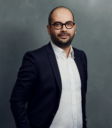Meet the Team of experts - Photo of Danilo Samà, person in business suit, glasses with dark frames, smiling, male, gallantly, standing upright
