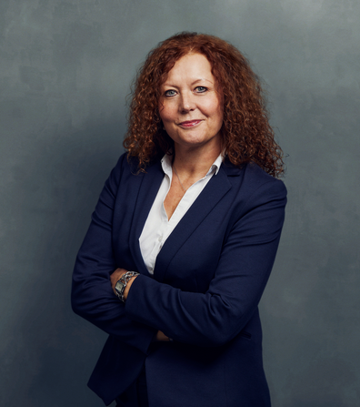 Meet the Team of experts - Photo of Ilona Louis, person in business suit, smiling, female, friendly, standing upright, crossed arms