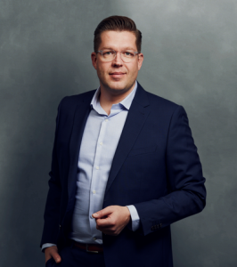Meet the Team of experts - Photo of Jakob Rüggeberg, person in business suit, glasses, smiling, male, gallantly, standing upright